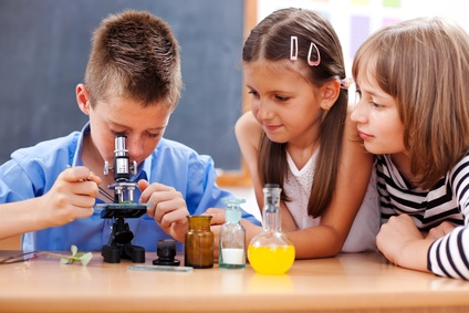 Boy looking into microscope - Eminent elementary school boy looking into microscope while girls are watching
